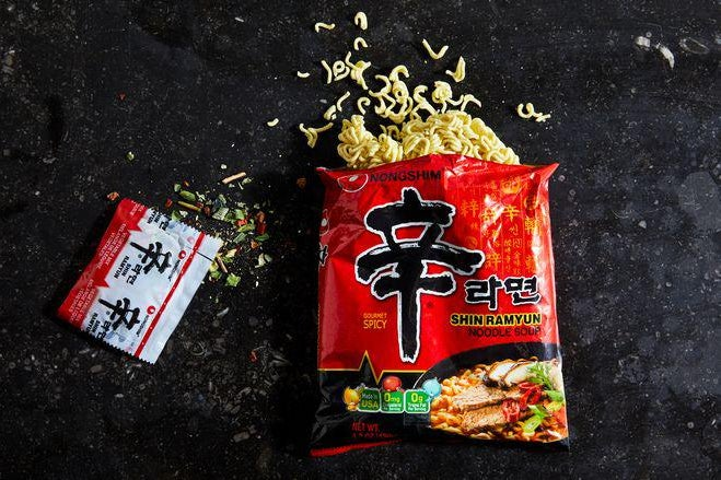 Hard noodles spill out of a packet of Shin Ramyun.