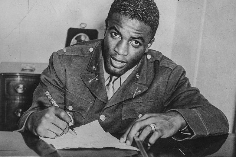 Robinson, seated, looks toward the camera as he signs paperwork at a desk