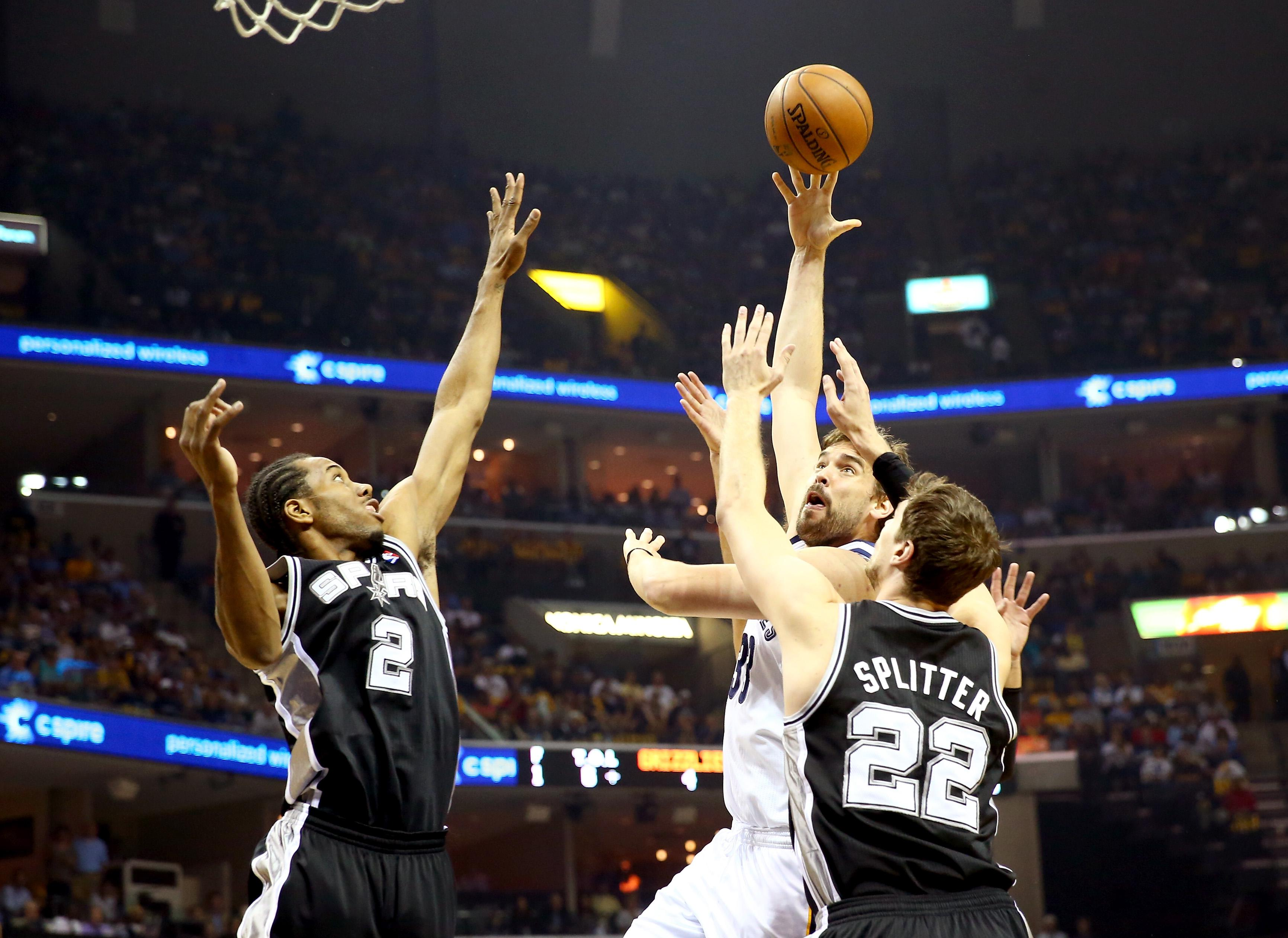 Marc Gasol, No. 33 of the Memphis Grizzlies, goes up for a shot against Tiago Splitter, No. 22 and Kawhi Leonard, No. 2 of the San Antonio Spurs, in the first quarter during Game 4 of the Western Conference Finals of the 2013 NBA Playoffs at the FedExForum on May 27, 2013, in Memphis, Tenn.