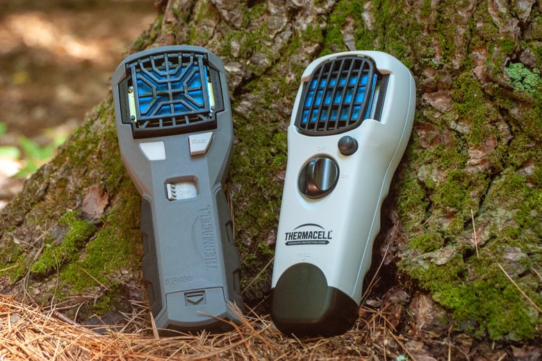 two Thermacell units resting against a tree trunk