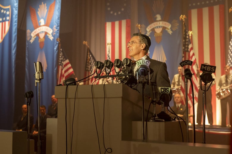 "John Turturro, in a still from The Plot Against America, stands at a podium in front of a wall covered with ""America First"" banners. He is smiling."