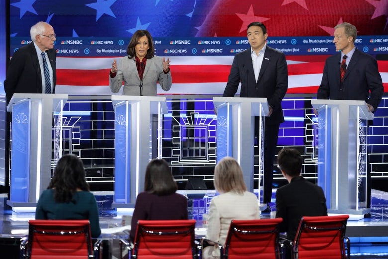 Harris speaks as three other candidates are pictured looking on. The backs of the four debate moderators are seen in the foreground.