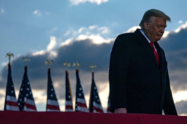 Trump looks down and turns away from a handful of American flags in the background.