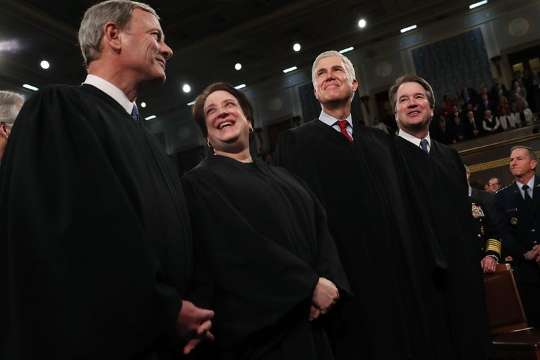 Justice Elena Kagan laughs while Chief Justice John Roberts smiles and Justices Neil Gorsuch and Brett Kavanaugh grin at someone or something in the distance.