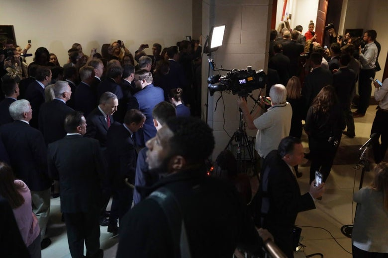 A large group of white men wearing suits surrounds an open door as reporters and photographers look on.