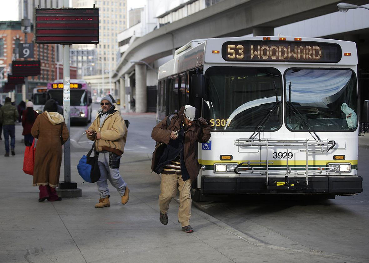 Commuters exit the 53 Woodward bus at the Rosa Parks bus terminal January 1, 2015 in Detroit, Michigan.