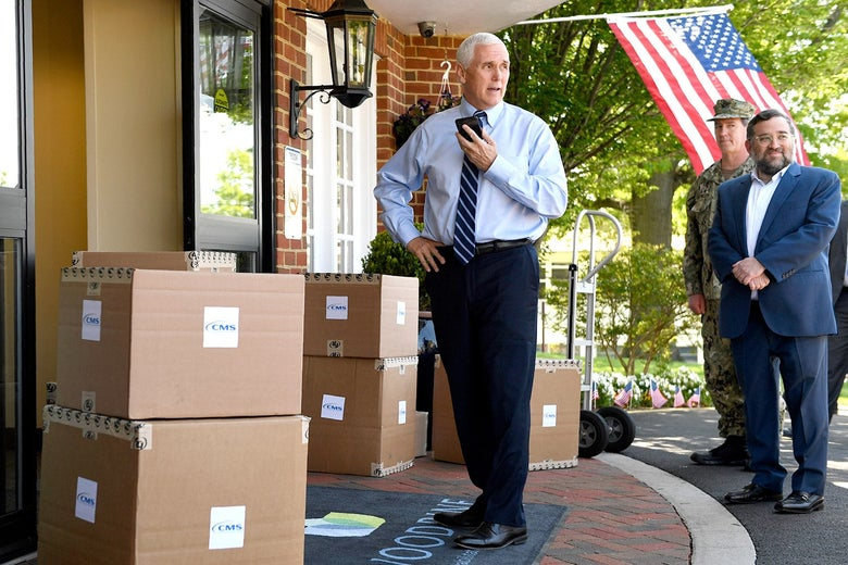 Pence, wearing a shirt and tie, speaks into a phone while standing next to piles of boxes.