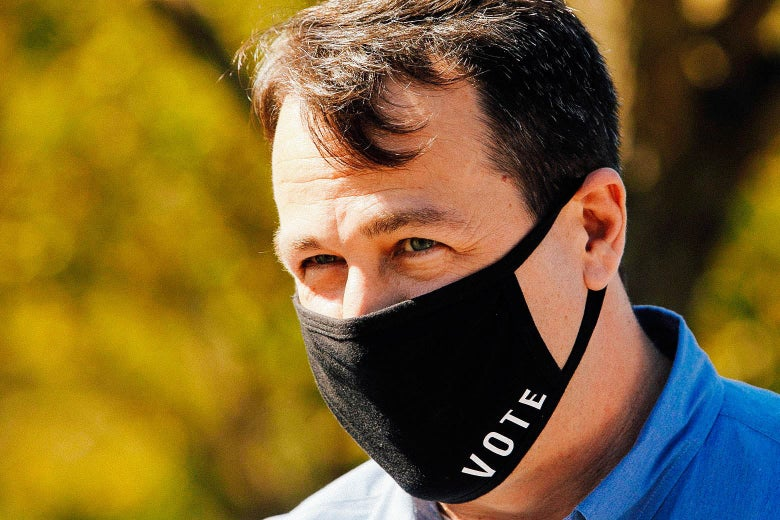 """Cal Cunningham wears a blue collared shirt and a black face mask that says """"vote"""" on it."""