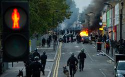 Riot police tackle a mob after a number of cars are set alight in Hackney, north London on August 8, 2011. Click image to expand.