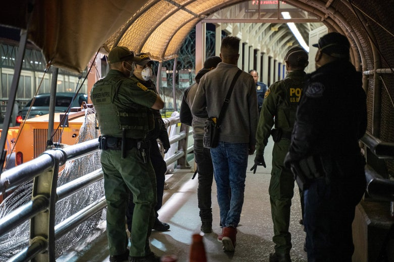Uniformed CBP officers stand beside asylum-seekers in a covered walkway