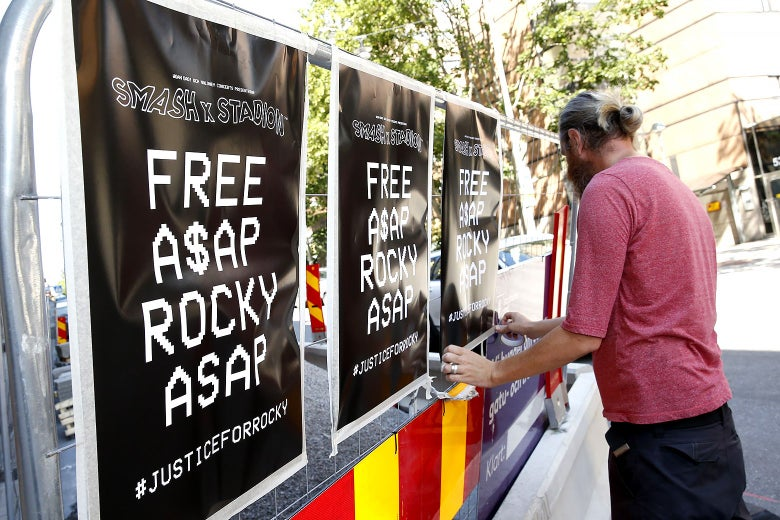 A man displays posters advocating for ASAP Rocky's release.