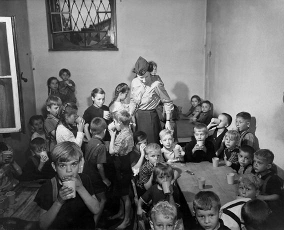 An American Army Public Health nurse with a group of children in a camp for Polish displaced persons at Bensheim,Germany on June 19, 1945.