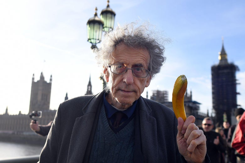 An older man with wild hair holds up a banana while standing outside in London.