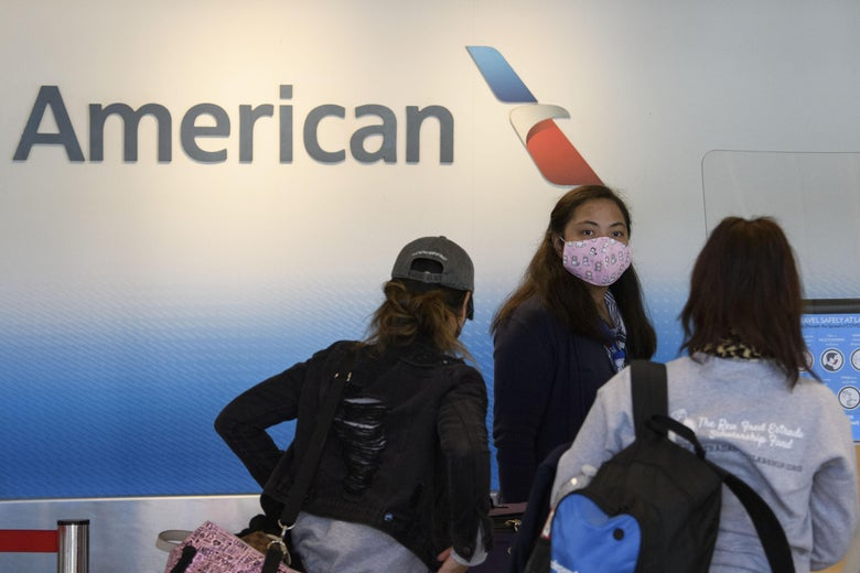 A masked American Airlines agent checks in travelers.