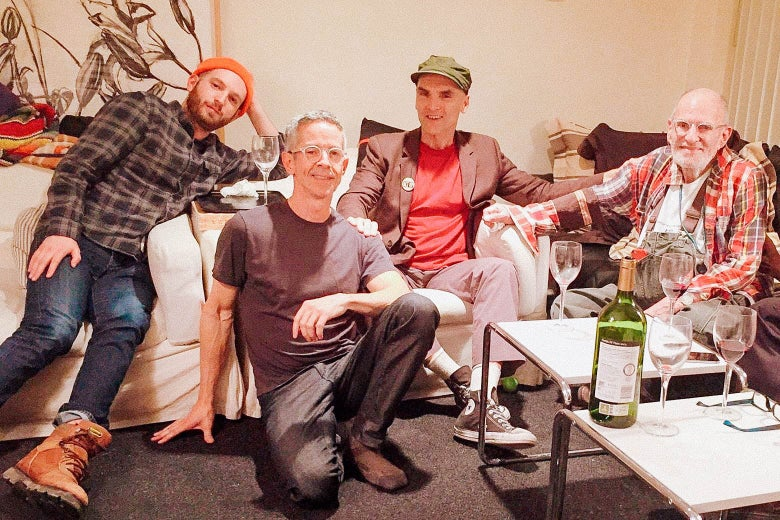 Four men pose together on sofas and chairs in a living room with a wine bottle and wine glasses on a nearby coffee table.