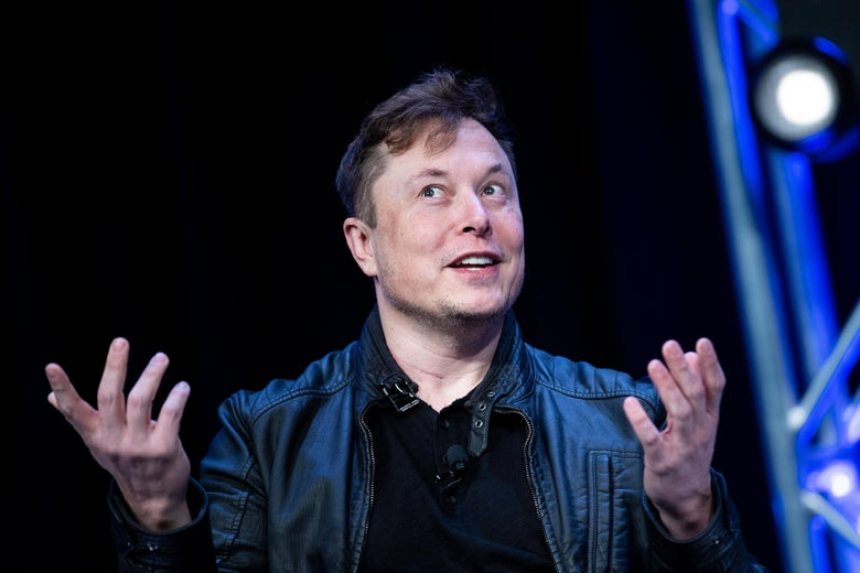 A wide-eyed Elon Musk holds his hands apart as he speaks on a stage.