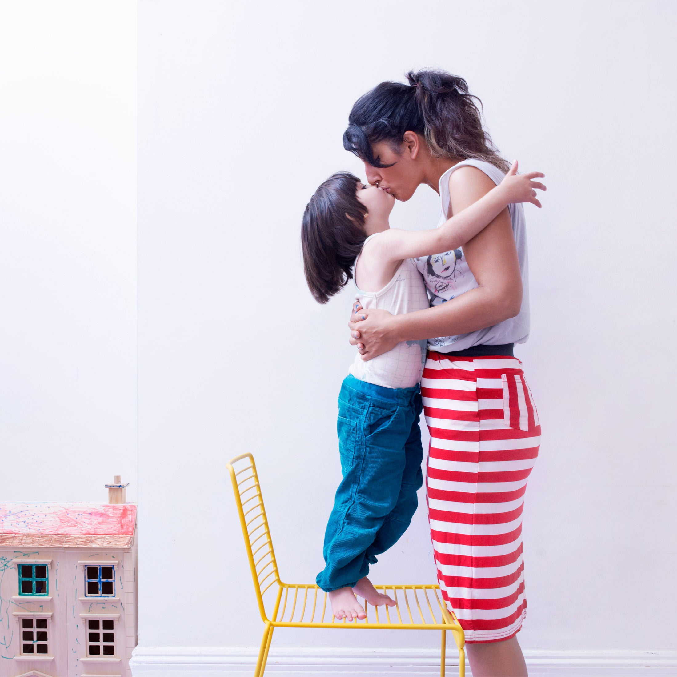 Young child standing on a chair smooching his mom.