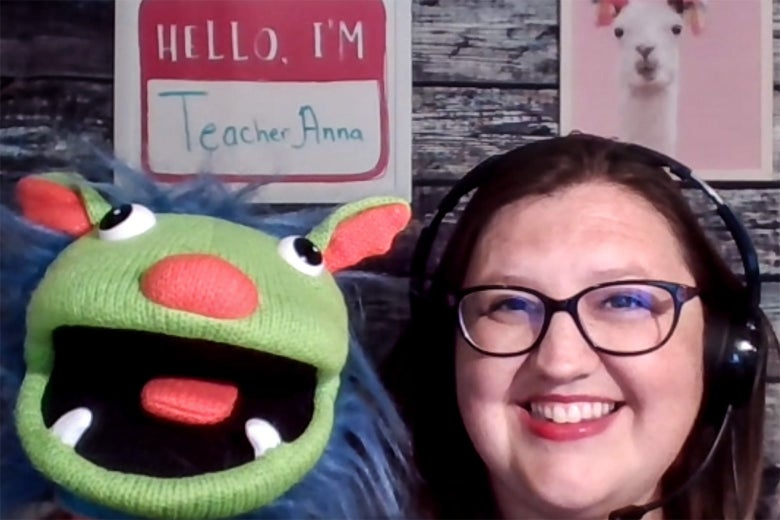 A woman in glasses and headphones with a puppet.
