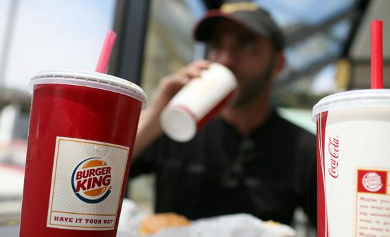 A Burger King customer drinks a soda while eating lunch at a Burger King.