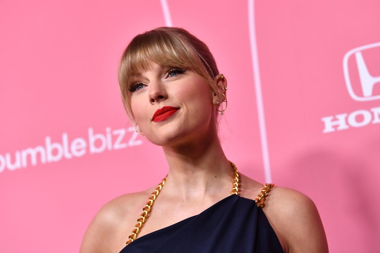 Taylor Swift in front of a pink background.