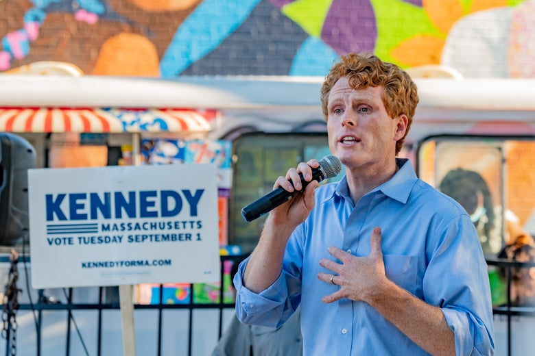 Joe Kennedy holds a microphone in one hand and his other hand to his chest while speaking in front of a mural.
