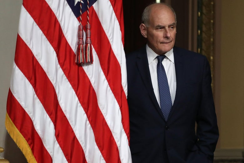 John Kelly stands next to an American flag.