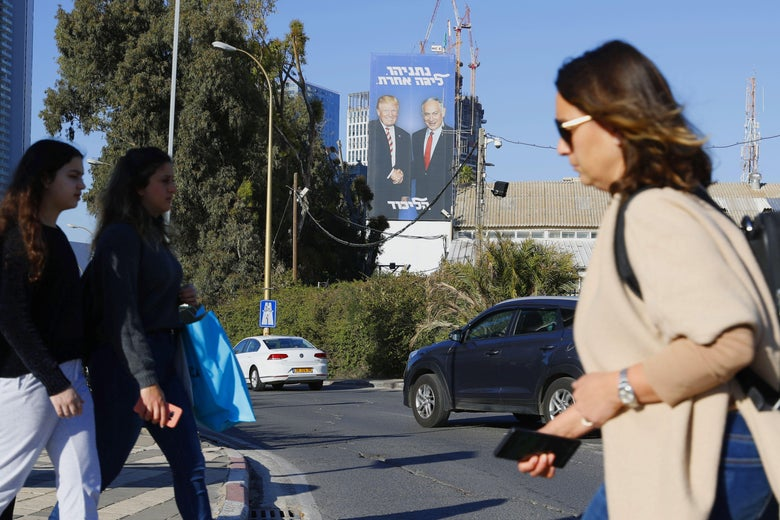 Pedestrians cross a street in front of a giant election billboard showing Israeli Prime Minister Benjamin Netanyahu and U.S. President Donald Trump shaking hands, in the Israeli coastal city of Tel Aviv on Feb. 3