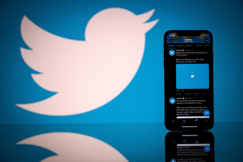 A phone displaying Twitter's logo, in front of another image of the Twitter logo.