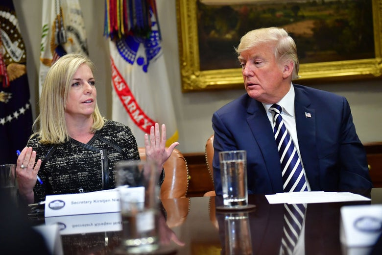 Nielsen gestures as Trump looks on while both are seated at a roundtable-style event.