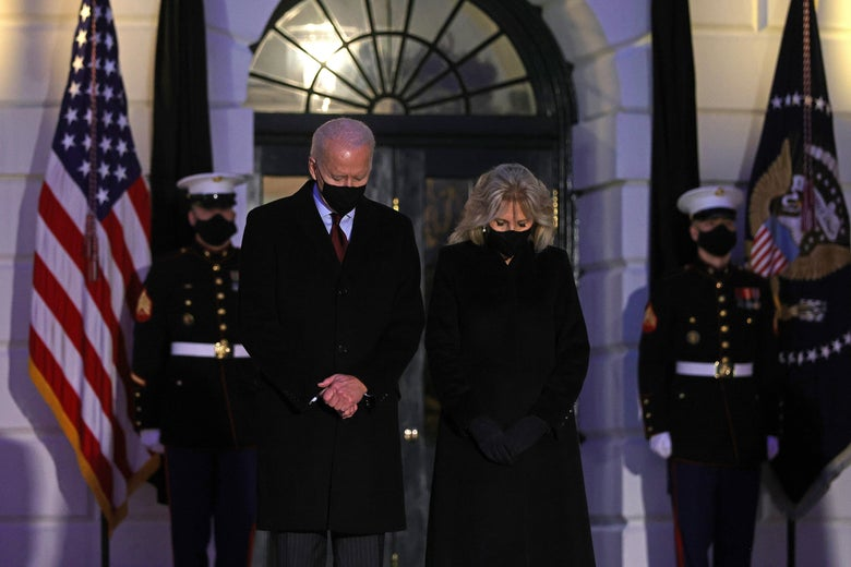 The Bidens bow their heads for a moment of silence outside the White House.