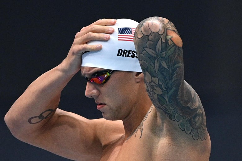 Dressel shirtless and in goggles adjusting his swimming cap (sporting his last name and American flag), with visible tattoos on his arms and left shoulder.