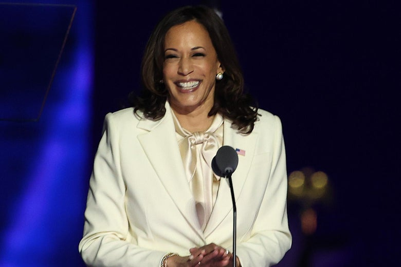 Kamala Harris, wearing a white pantsuit, grins onstage at a podium