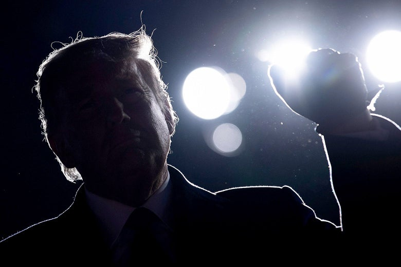 Donald Trump against a dark night sky with large flood lights behind him.