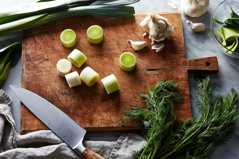 A cutting board laden with sliced leeks, garlic cloves and a garlic bulb. Whole leeks and another garlic bulb peek out from the top, fresh dill comes up from the bottom. A knife rests on the cutting board.
