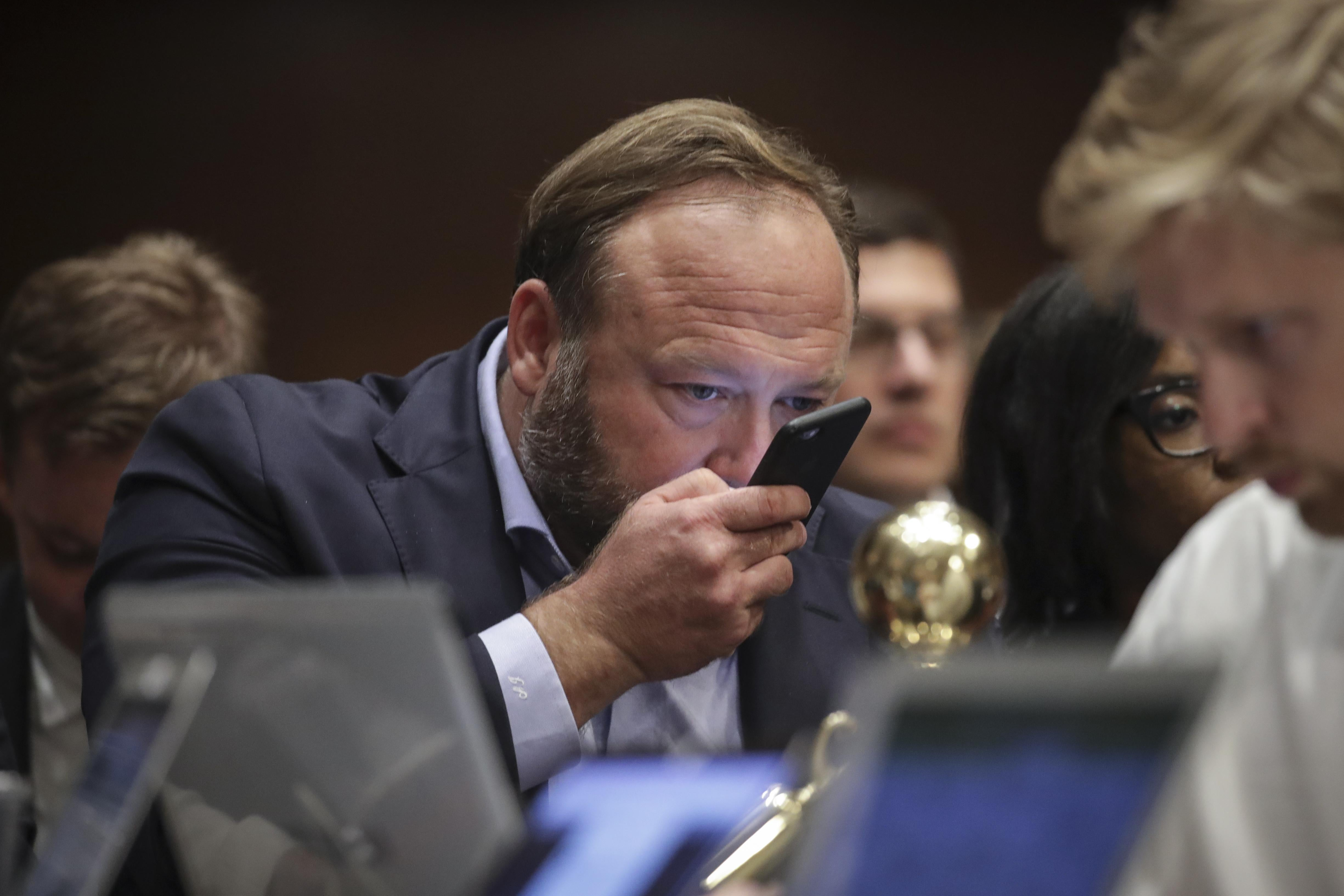 WASHINGTON, DC - SEPTEMBER 5: Alex Jones of InfoWars speaks into his phone during a Senate Intelligence Committee hearing concerning foreign influence operations' use of social media platforms, on Capitol Hill, September 5, 2018 in Washington, DC. Twitter CEO Jack Dorsey and Facebook chief operating officer Sheryl Sandberg faced questions about how foreign operatives use their platforms in attempts to influence and manipulate public opinion. (Photo by Drew Angerer/Getty Images)