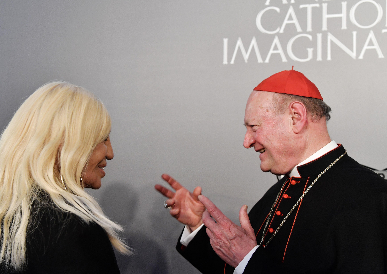Italian designer Donatella Versace speaks to cardinal Gianfranco Ravasi.