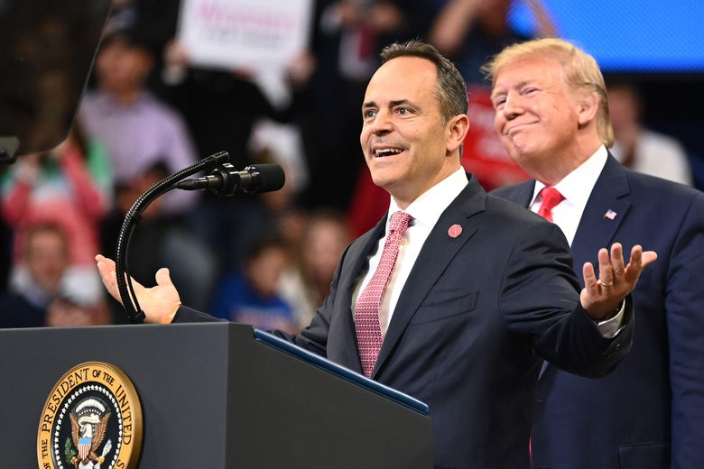 Trump smiles while standing behind Matt Bevin, who is giving a speech at a podium.