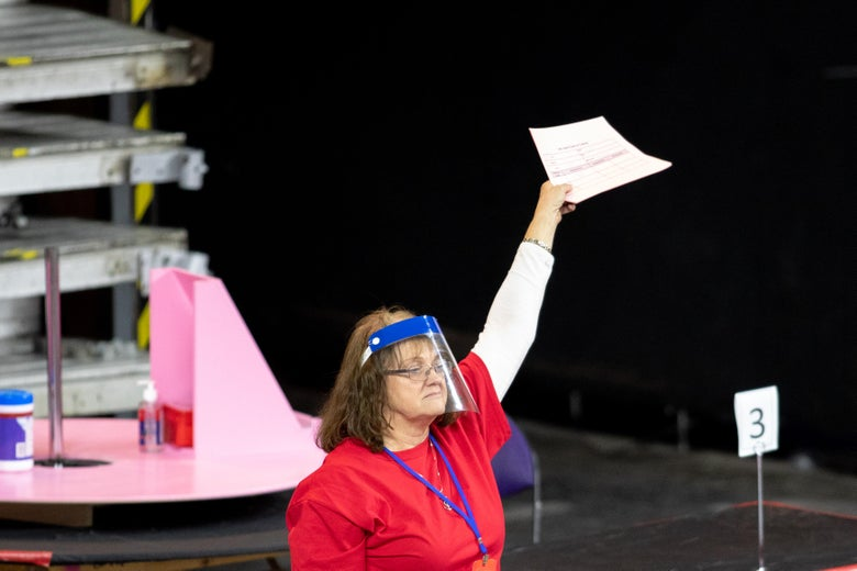 A woman wearing a visor holds up a piece of paper in the recount facility.