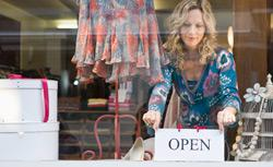 Shop keeper putting open sign in window. Click image to expand.