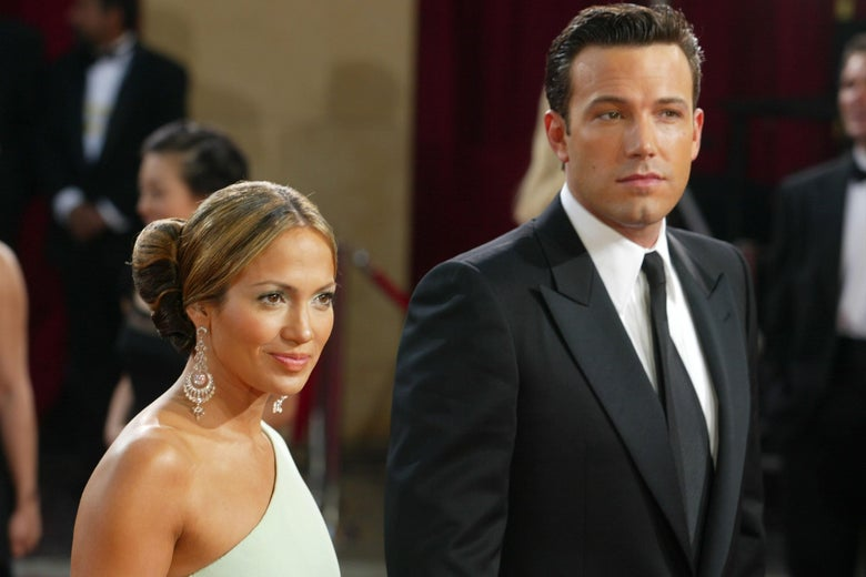 Jennifer Lopez in a one-shoulder white dress and Ben Affleck in a suit on the red carpet