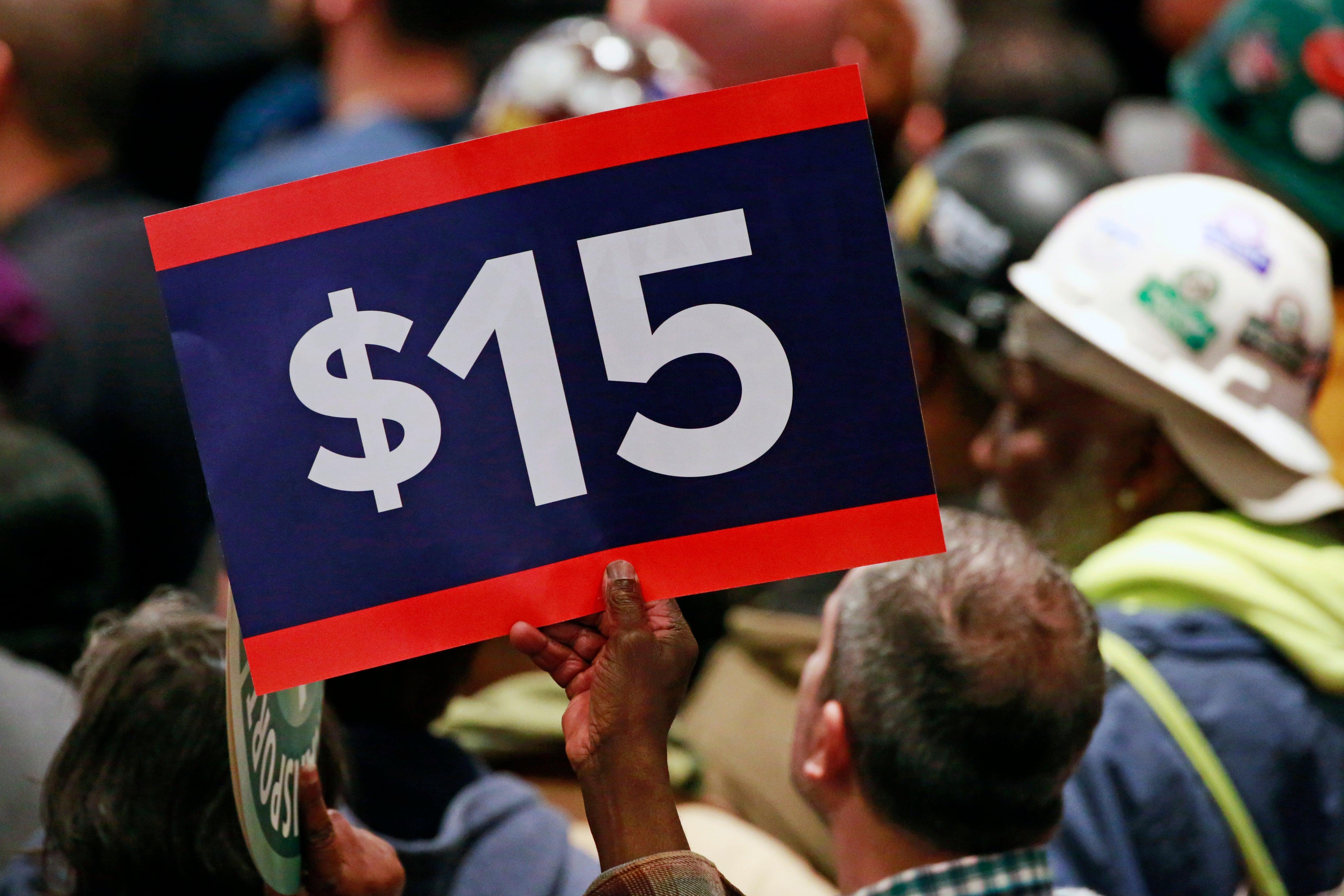 A worker holds up a sign demanding a $15 minimum wage