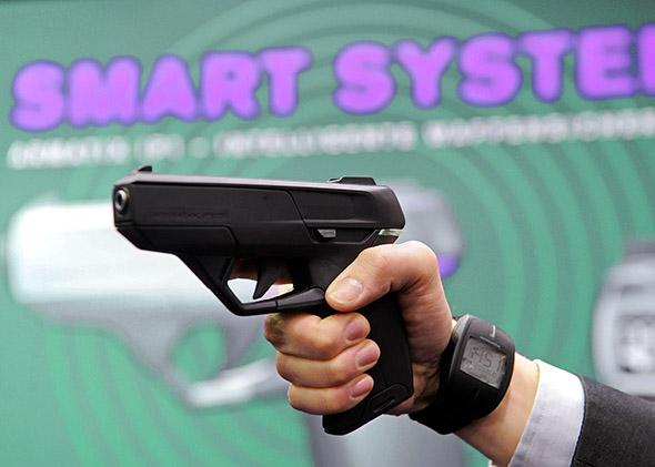 An employee of Armatix poses for photographers as he presents the €œSmartGun.