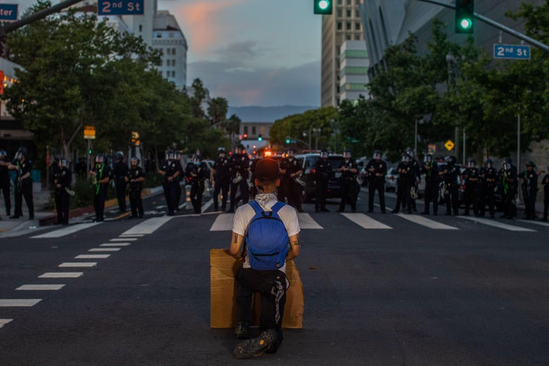 A demonstrator kneels in front of a Police line in Downtown Los Angeles on May 30, 2020.