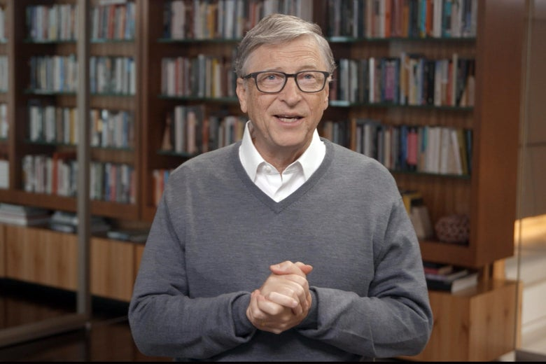 Bill Gates clasps his hands in front of bookshelves.