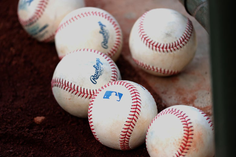 A bunch of baseballs on the ground.