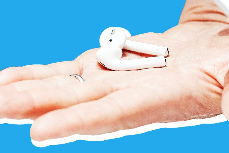 A hand with a wedding band holds a pair of AirPods.