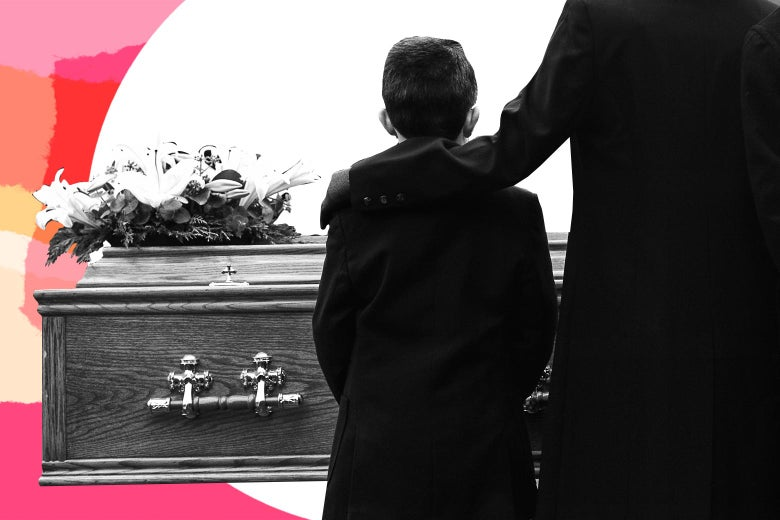 Boy dressed in a black with his mother's arm around him in front of a casket.