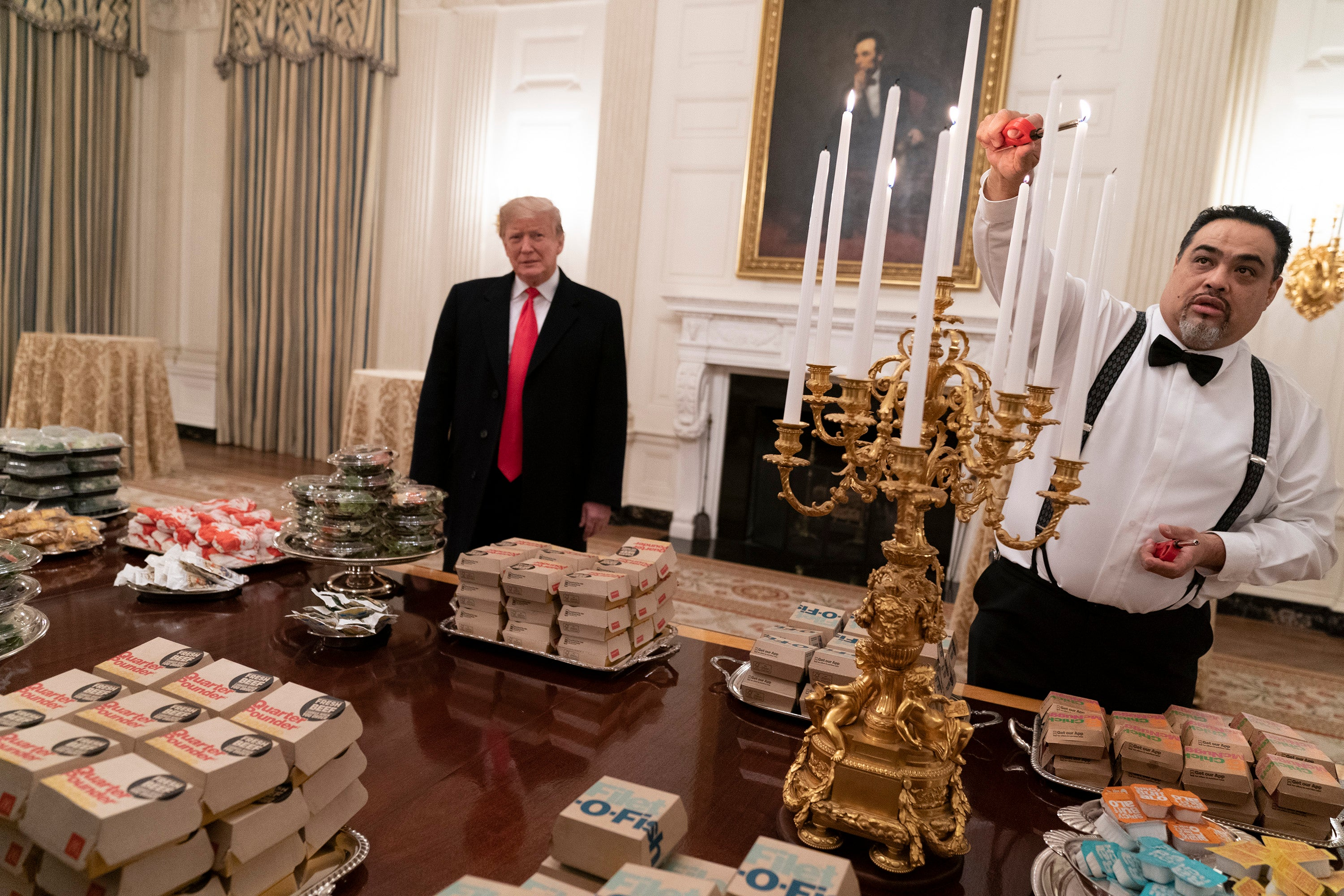 Trump stands in front of a table covered in fast food with a portrait of Abraham Lincoln behind him.