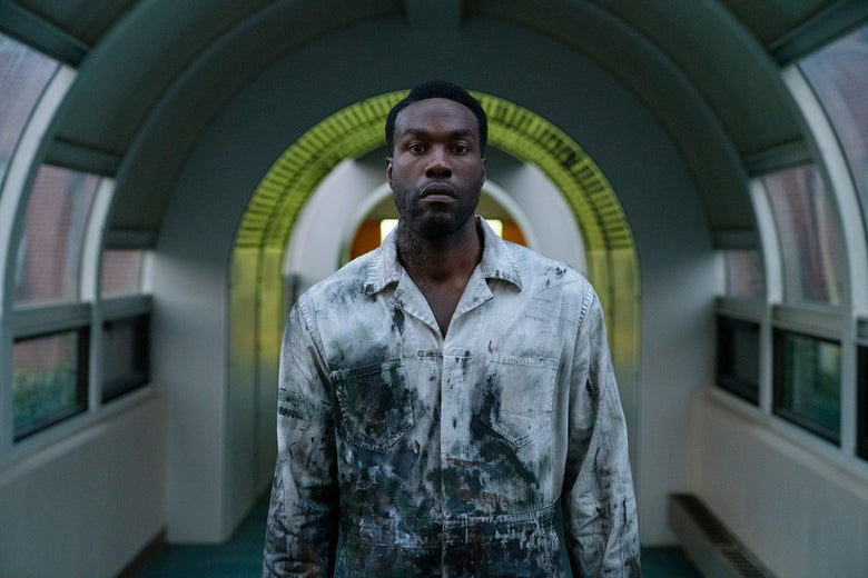 A man in a paint-splattered jumpsuit stands in an empty hallway with white walls and big windows. He stares straight ahead.