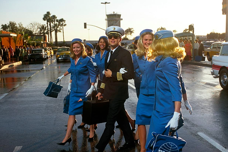 Leonardo DiCaprio in a pilot suit walks with a group of flight attendants.